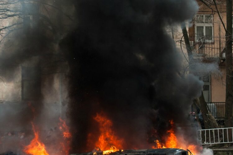 car destroyed and set on fire during the riots. city center. clouds of smoke